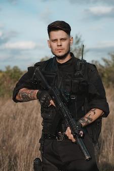 Молодой солдат в черной форме с автоматом