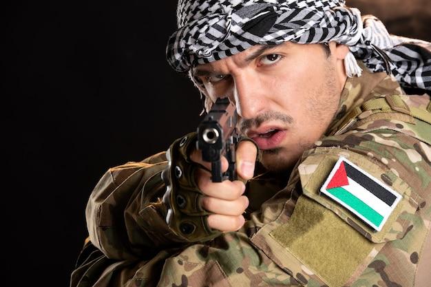 어두운 벽에 총으로 싸우는 위장에 젊은 군인