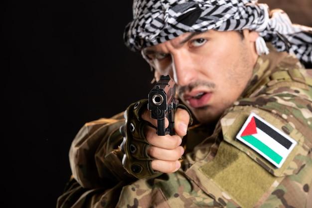 Молодой солдат в камуфляже борется с ружьем на темной стене