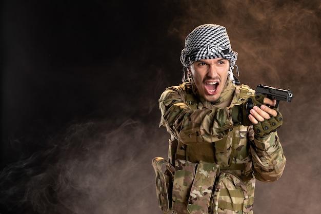 연기가 자욱한 어두운 벽에 총을 들고 위장에 젊은 군인
