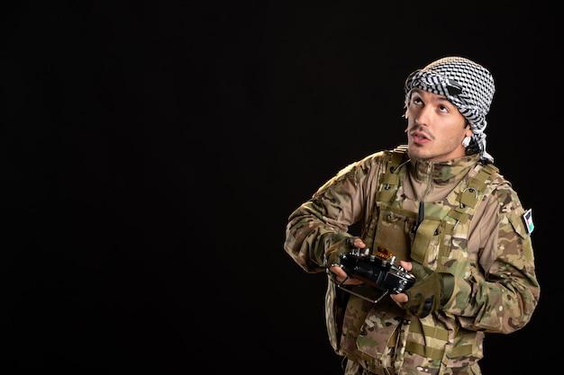 검은 벽에 원격 컨트롤러를 사용하여 위장에 젊은 군인