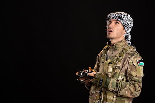 어두운 벽에 원격 컨트롤러를 사용하여 위장에 젊은 군인