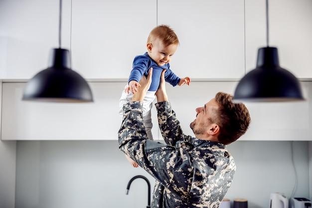 若い兵士が家に着いたばかりで、息子に会えてとても幸せです。男は幼児を持ち上げています。