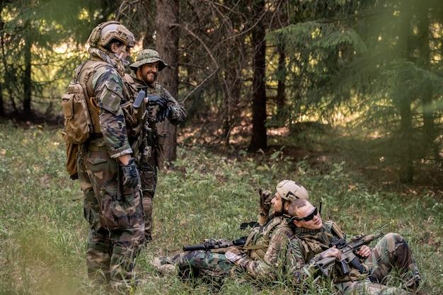 잔디에 등을 맞대고 앉아 숲에서 쉬면서 동료들과 이야기하는 젊은 군인