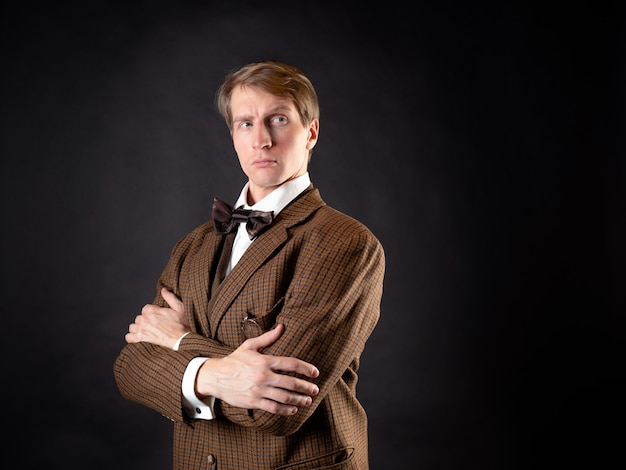 A young, solid man in the image of a victorian scientist, a university teacher or a natural scientist. vintage retro suit, young attractive man in a vest and bow tie