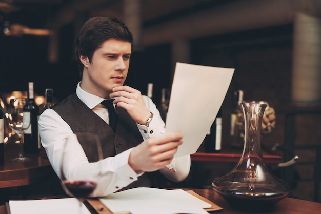 Young sommelier looks thoughtfully at wine list.