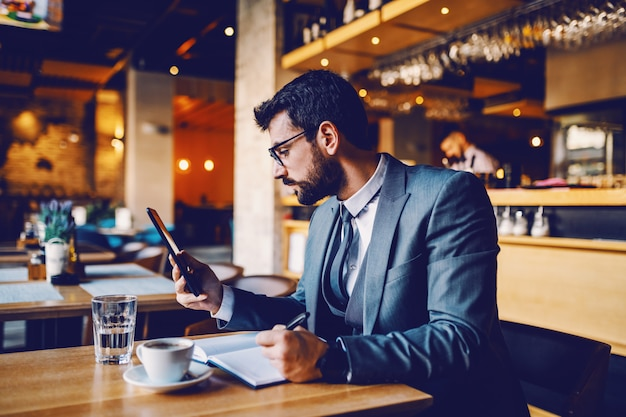Young sophisticated caucasian lawyer in suit with eyeglasses sitting in cafe, looking at tablet and writing important things about case in notebook.