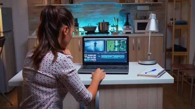 ポストプロダクション中にビデオ映像に取り組んでいる若いサウンドエンジニア。深夜に処理するための最新のソフトウェアを使用した、映画のモンタージュのホーム編集におけるコンテンツ作成者。