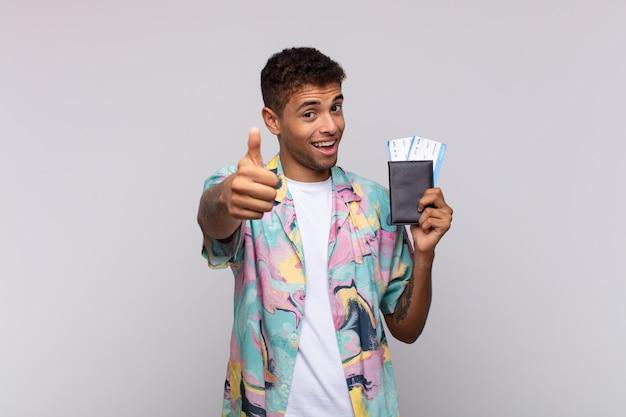 자랑스럽고, 평온하고, 자신감 있고, 행복하고, 엄지 손가락으로 긍정적으로 웃고있는 젊은 남미 남자