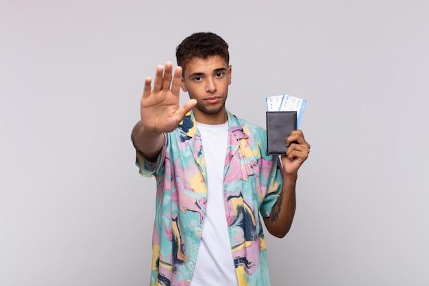 真面目で、厳しく、不機嫌で、怒っているように見える南米の若い男が、手のひらを開いてジェスチャーを止めている