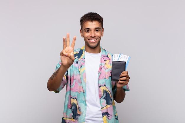 笑顔でフレンドリーに見える南米の若い男、前に手を出して3番目または3番目を示し、カウントダウン