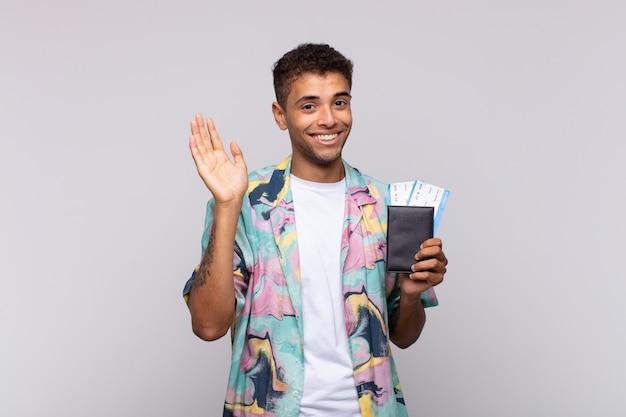 행복하고 유쾌하게 웃고, 손을 흔들며, 환영하고 인사하거나, 작별 인사를하는 남미 젊은이