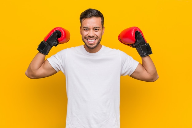 Young south asian boxer man wearing red gloves.