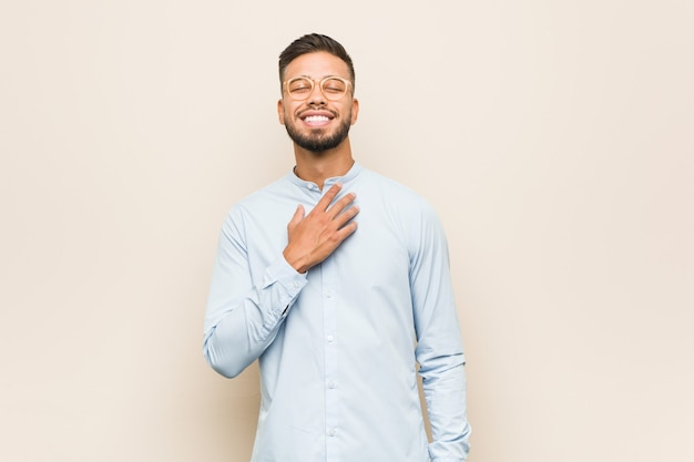 Young south-asian business man laughs out loudly keeping hand on chest.