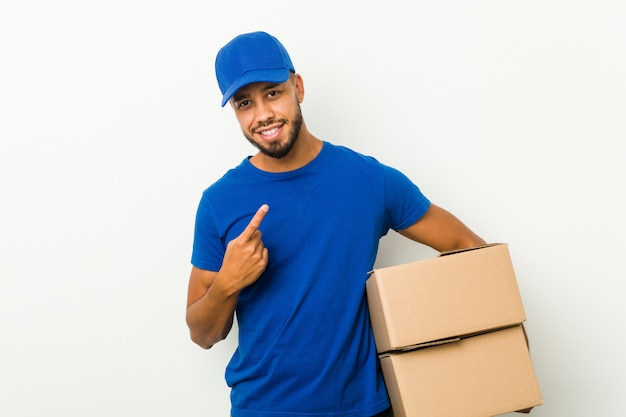 Young south-asian delivery man pointing with finger at you as if inviting come closer.