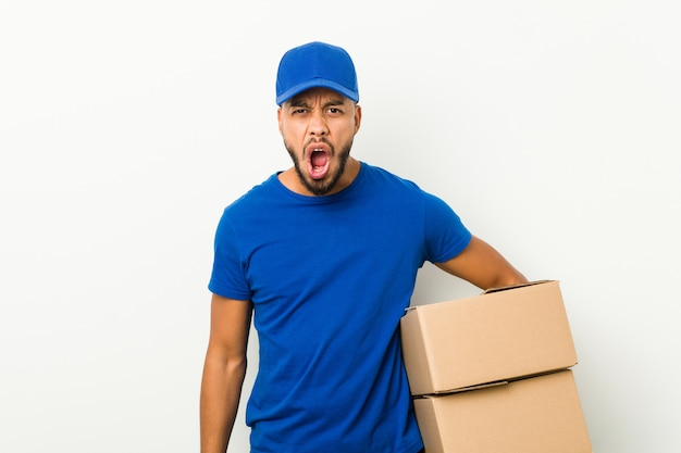 Young south-asian delivery man screaming very angry and aggressive.