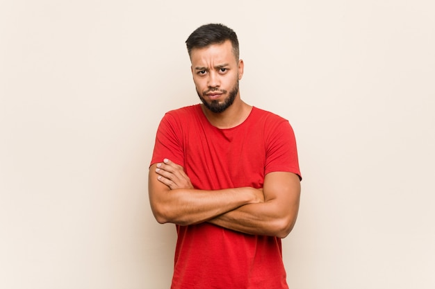 Young south-asian man frowning face in displeasure, keeps arms folded.