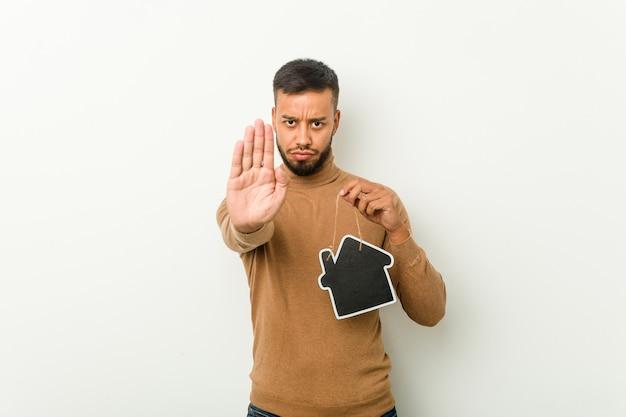 一時停止の標識を示す伸ばした手で立っている家のアイコンを保持し、あなたを妨げる南アジアの若い男。