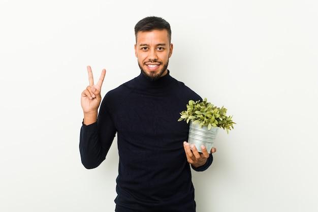 南アジアの若者が指で2番目を示す植物を保持しています。