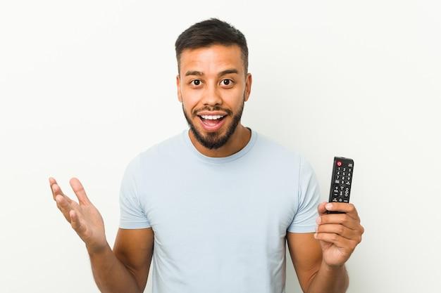 Молодой человек из южной азии, держащий контроллер телевизора, получает приятный сюрприз, взволнован и поднимает руки.