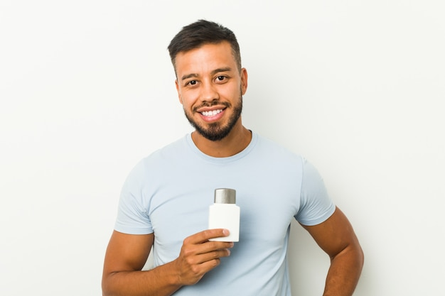 Young south-asian man holding an after shave cream happy, smiling and cheerful.