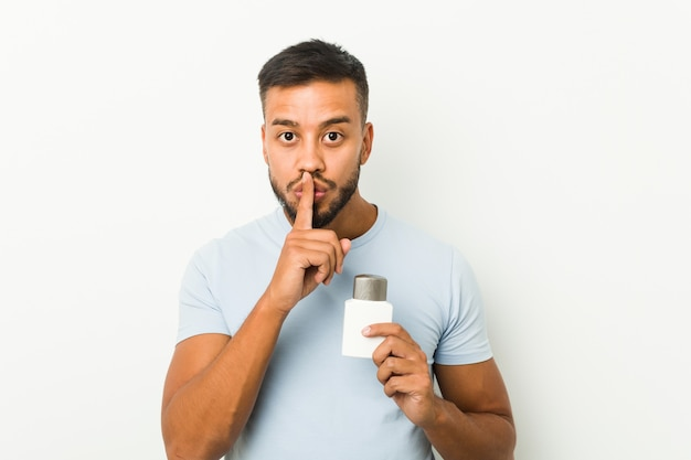 Young south-asian man holding an after shave cream keeping a secret or asking for silence.