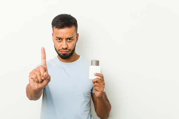 Young south-asian man holding an after shave cream showing number one with finger.