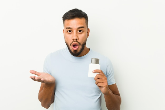 Young south-asian man holding an after shave cream surprised and shocked.