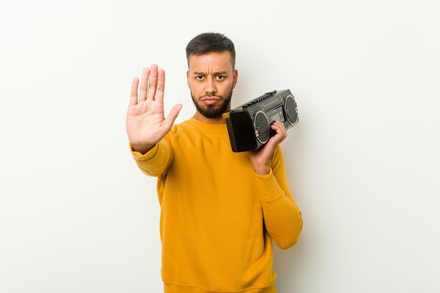 Young south-asian man holding a guetto blaster standing with outstretched hand showing stop sign, preventing you