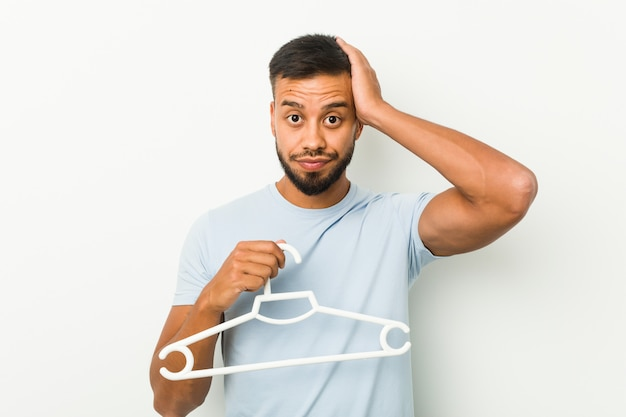 Young south asian man holding a hanger being shocked, she has remembered important meeting.