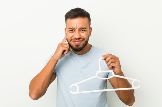 Young south asian man holding a hanger covering ears with hands.