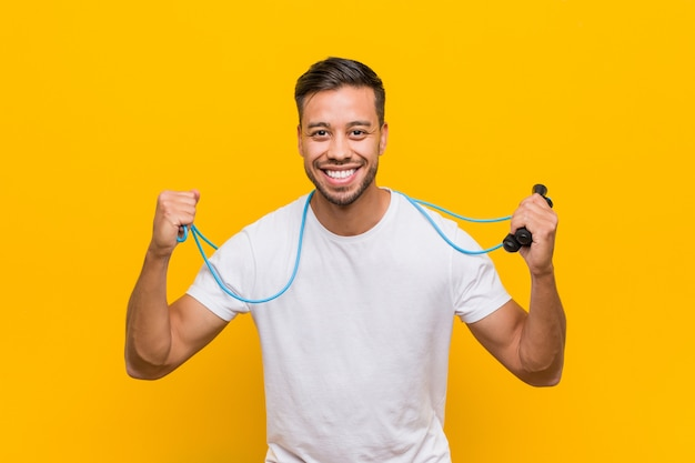 Young south-asian man holding a jump rope.