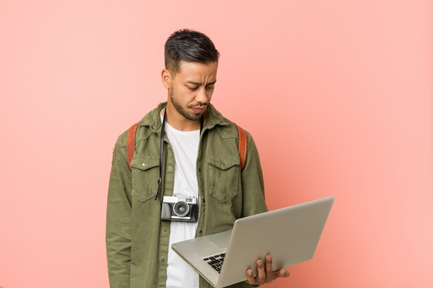 Young south-asian man holding a laptop.