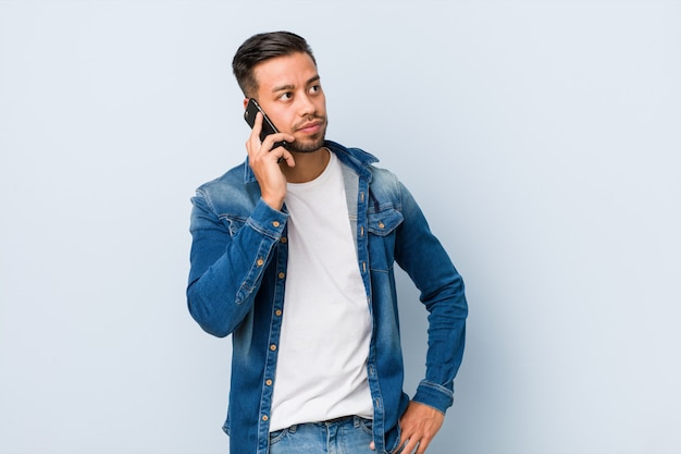 Young south-asian man holding a phone