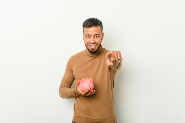 Young south-asian man holding a piggy bank cheerful smiles pointing to front.