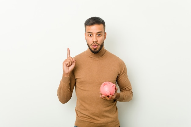 Young south-asian man holding a piggy bank having some great idea