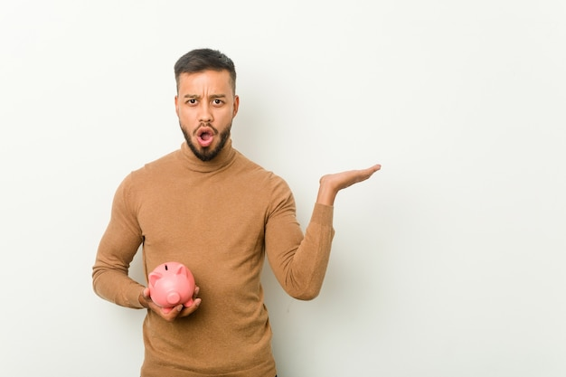 Young south-asian man holding a piggy bank impressed holding copy space on palm.
