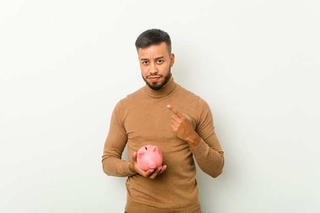Young south-asian man holding a piggy bank pointing with finger at you as if inviting come closer.