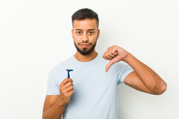 Young south-asian man holding a razor blade showing a dislike gesture, thumbs down. disagreement concept.