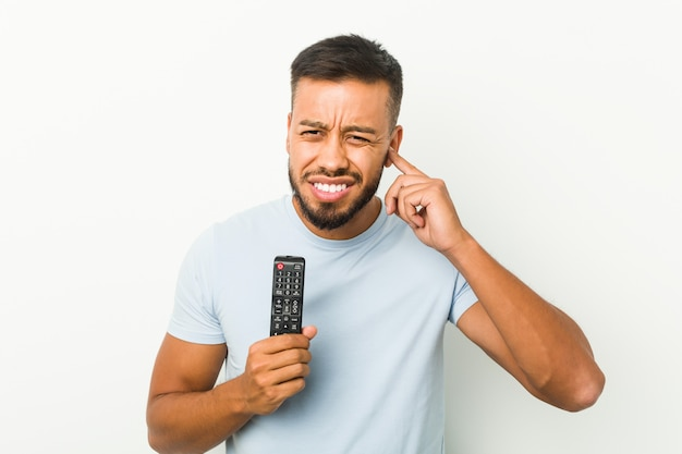 Young south-asian man holding a tv controller covering ears with hands.
