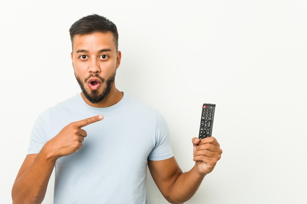 Young south-asian man holding a tv controller pointing to the side