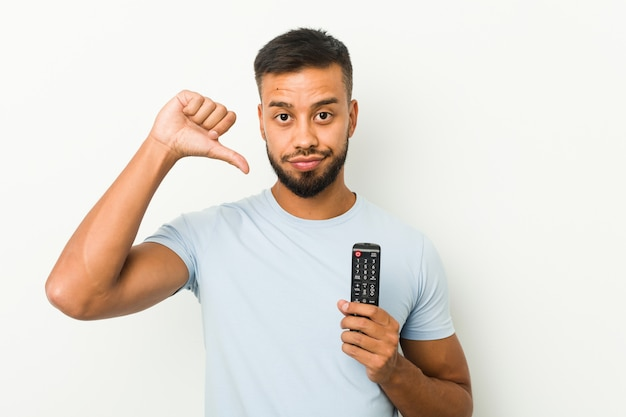 Young south-asian man holding a tv controller showing a dislike gesture, thumbs down. disagreement concept.