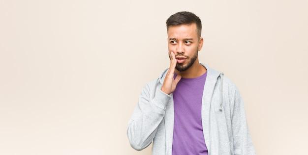젊은 남아시아 남자가 비밀스러운 제동 뉴스를 말하고 옆으로보고있다.