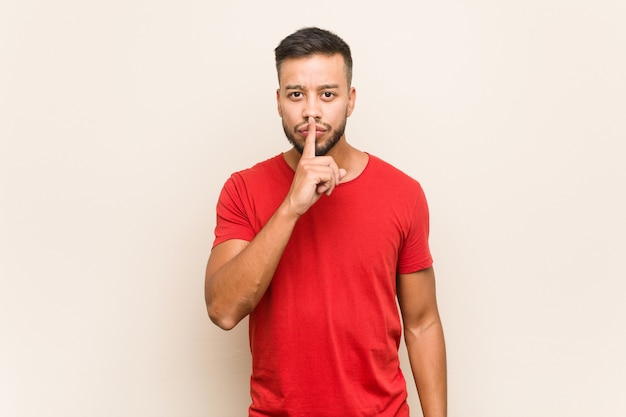 Young south-asian man keeping a secret or asking for silence.