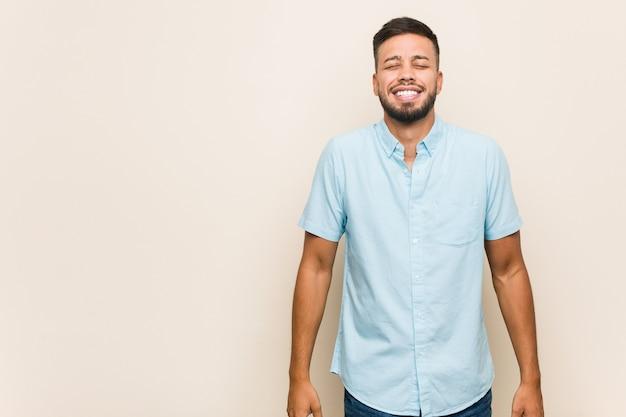 Молодой южноазиатский мужчина смеется и закрывает глаза, чувствует себя расслабленным и счастливым.