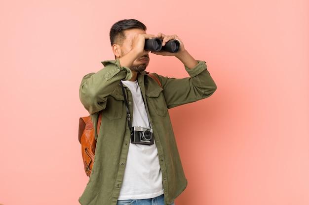 双眼鏡で見ている若い南アジア人。