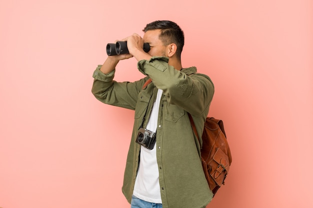 Young south-asian man looking through a binoculars.