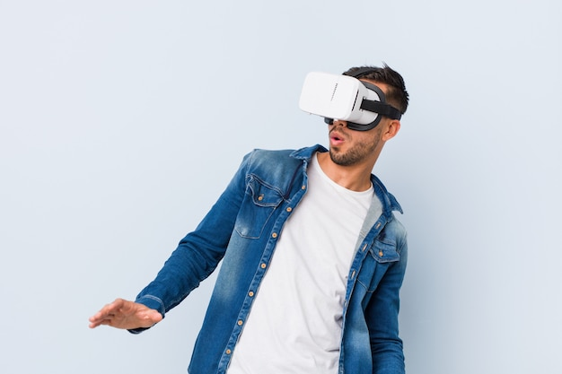 Young south-asian man playing with virtual reality glasses