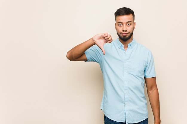 Young south-asian man showing a dislike gesture, thumbs down. disagreement concept.