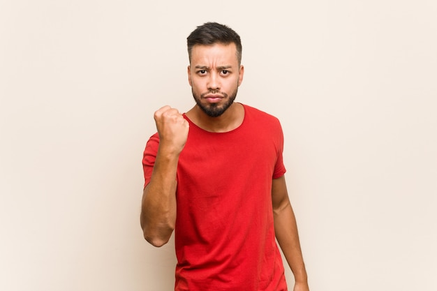 Young south-asian man showing fist to camera, aggressive facial expression.